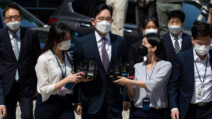 Jay Y. Lee, co-vice chairman of Samsung Electronics, center, wears a protective mask as he is surrounded by members of the media while arriving at the Seoul Central District Court in Seoul, South Korea, on Monday, June 8, 2020.